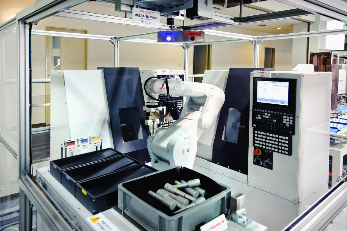 Showroom w Nagoya Works – widoczne m.in. maszyny i roboty przemysłowe ze zintegrowanymi systemami wizyjnymi, sterowane z wykorzystaniem platformy iQ.